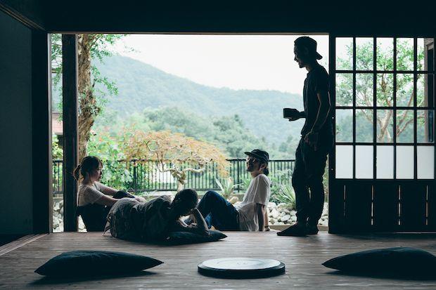 古民家の縁側でカップを手にくつろぐ男性や肩肘をついて寝転がる女性