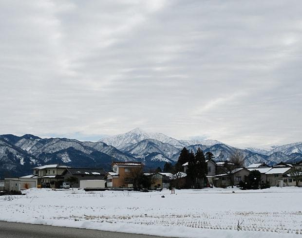 雪におおわれた山々と麓に広がる住宅
