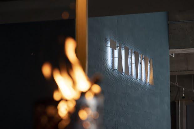 焚き火を囲む新しいビジネス合宿施設「TAKIVIVA(タキビバ)」のロゴプレート