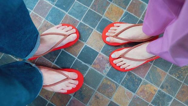 素足に赤い〈Waraji Sandals〉を履いた二人分の足元