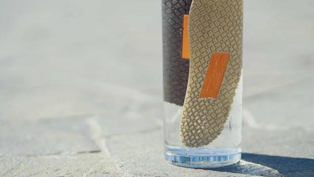 石畳に置かれた水入り容器の中に浮かぶ〈Waraji Sandals〉のアウトソール2枚
