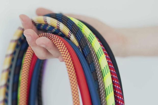 カラフルな組紐の束を持つ手