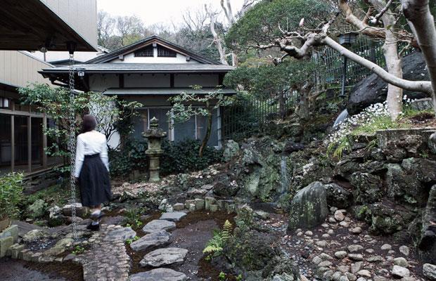 暖簾がかかる門をくぐったところにある中庭。湧き水を利用した滝が庭に水を流している。(撮影:甲田和久)