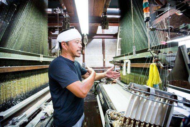 工場の一番奥にあるシャトル織機を紹介してくれた〈遠孫織布株式会社〉代表取締役社長の遠藤由貴さん。