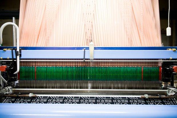 奥から古い順番に織機が並んでいて、工場の歴史を感じる。