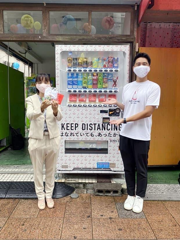 宮崎市の西橘通にあるマスク自販機前で、マスクを手にする〈高原ミネラル〉専務の成松さん(左)