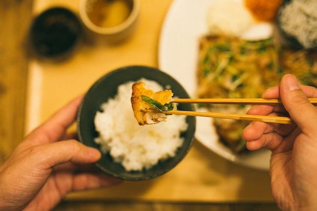 左手にごはん茶碗、右手に竹箸を持って食事をしている手元