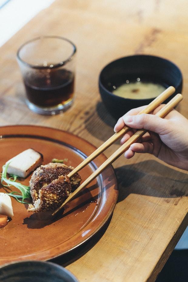 竹箸を使って食事をしている様子
