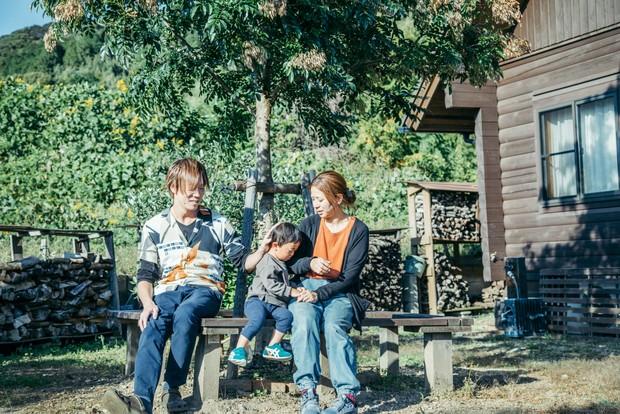 """庭のベンチでくつろぐ家族3人。丸留くんはちょっと""""おねむ""""。"""