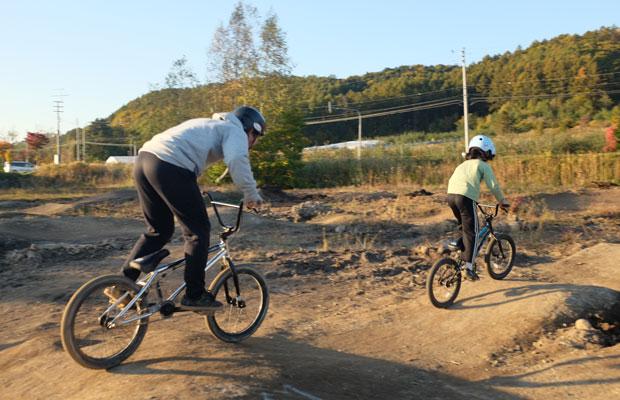 子どものうしろからアドバイスをする瀬尾さん。慣れない小さな子には自転車を手で支えながらコースを走ってくれる。