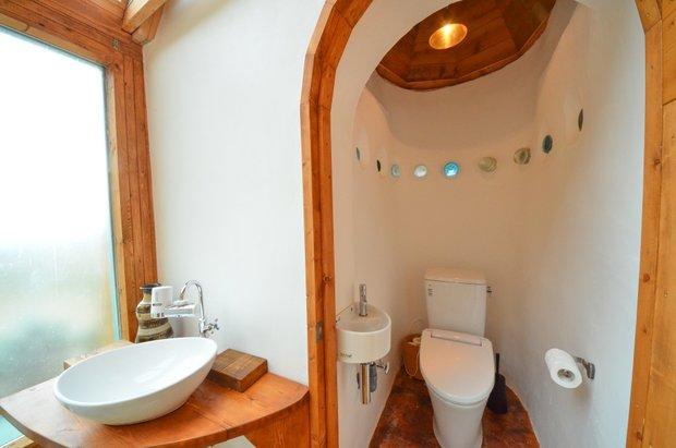 水洗トイレを完備。建築資材の空き瓶を一部見せ、この小さな空間までアースシップならではのデザイン性がうかがえる。