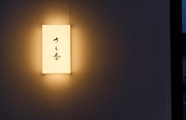 夜になると行燈看板に光が灯る。建物正面は真っ白な壁にシンプルなこの看板がひとつだけ。
