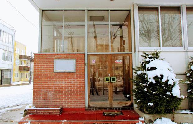 2階建の歯科医院兼住居。レンガと大きなドアや窓枠が特徴のエントランス。