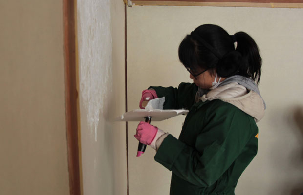 居間に漆喰を塗るボランティアの高校生。