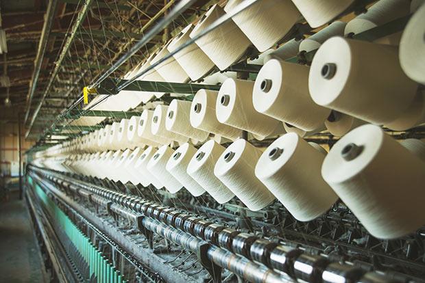 緯糸(横糸)の撚糸工場。上から下へ巻き取る際に糸をひねり、撚りをかける。撚りを安定させるため蒸す工程も。