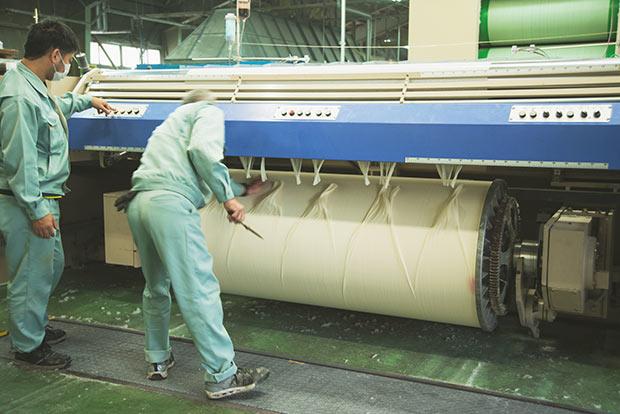 こちらは整経(縦糸を整える)工場の最終段階。ビームと呼ばれる筒状の器具に、糊づけされた数千本の糸が巻き取られる。