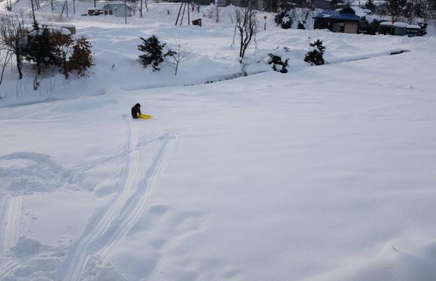 子どもたちはいつでも元気。家の前のマイゲレンデでソリ滑り。