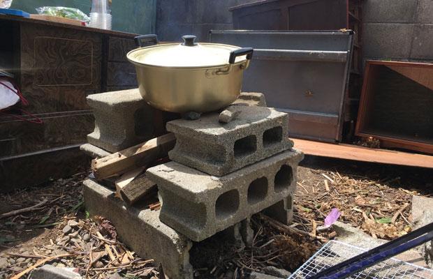 パーティにて、庭のコンクリートブロックを積み、廃材を燃やして煮物をつくる。都会では考えられない。