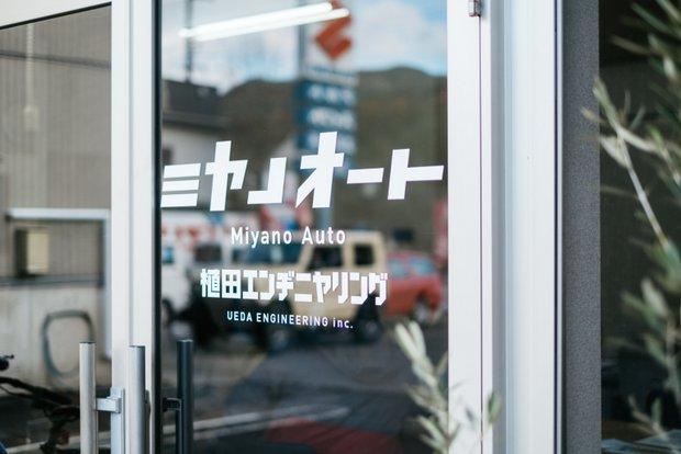 事務所のドア。屋号のミヤノオートはあくまで大きく、法人名の植田エンヂニヤリングは小さく。植田さんの考え方がうかがえる。
