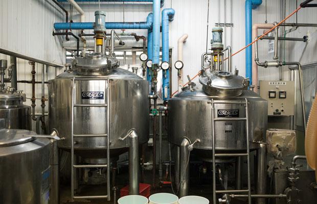 工場から約300メートルの湧出池から引く温泉水は約98度。熱交換機でその温泉水をエネルギーに変換し、工場の機器の動力として活用しています。写真はヨーグルトの発酵・殺菌を行う製造タンク。温泉の地熱で動いています。