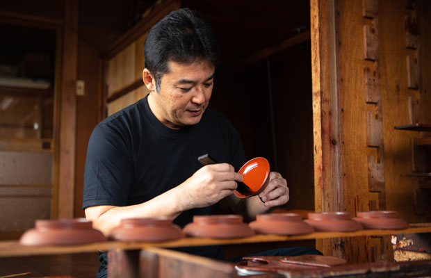 〈寿次郎〉の佐藤史幸さん。写真は中塗りの工程の様子。漆塗りの工程には下地塗り・中塗り・上塗りがあり、中塗りでは下地層の表面を滑らかにしていきます。