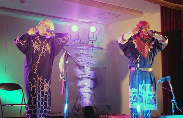 左がRekpoさん。右がOKIさん。口琴の一種といわれる竹製の楽器「ムックリ」の演奏。
