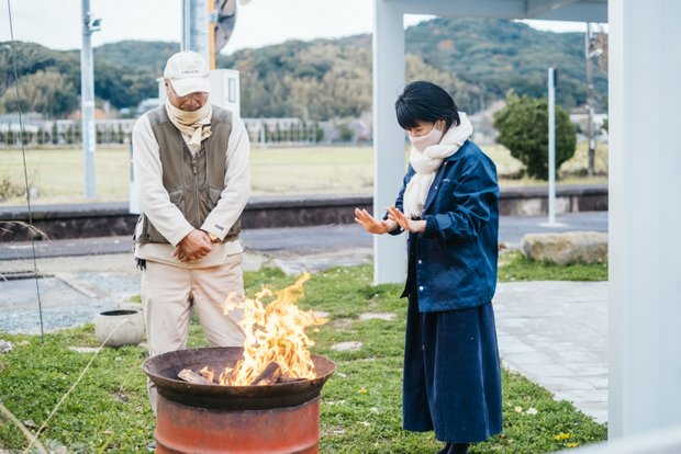 地元の人が持ってきてくれた薪で焚き火。取材中にも訪れてきた地元の人は皆、塩満さん、西野さんと会話を交わして帰っていく。それだけ地域に馴染んでいる証拠だ。