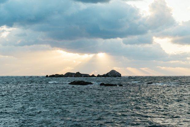 阿川駅から車で下関方面に進んだ先に広がる景色。深い青色の海原に夕陽が光り輝いていた。