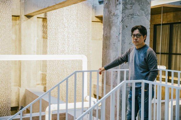 〈JINS〉の田中仁社長。エルリッヒさんの作品をバックに。