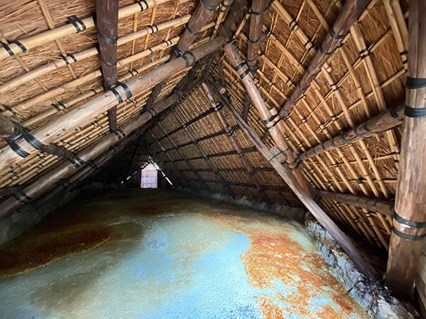 湯の花を生産するためのわら葺き小屋の内部。床(とこ)一面に広がるのが結晶化した湯の花。