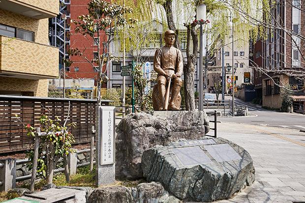 道後温泉駅前、坊っちゃんカラクリ時計の横にある正岡子規像。大の野球少年だった子規は、「打者」「走者」「四球」など、多くの野球用語を訳した。「まり投げて 見たき広場や 春の草」の句碑も。