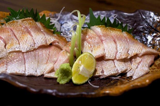 金坂さんの経営する〈海鮮焼き 浜心〉のノドグロの刺身。表面を炙って香ばしく。沖どれ一番の新鮮なものは脂のノリもよく、柑橘やわさびを利かせて食べる。舌の上でホロリとほどけていく柔らかさ。