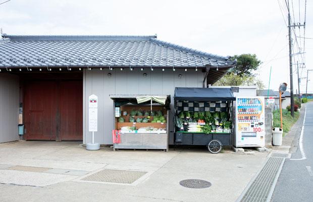 道行く車が、時折立ち寄っては野菜を買っていく直売所。左手に見えるのが赤門。