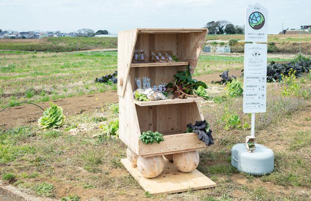 〈KHファーム〉に出現した直売所と看板(マークのデザインは、横須賀総合高等学校2年生の熊倉ひろさん)。木製の小屋が畑になじむ。