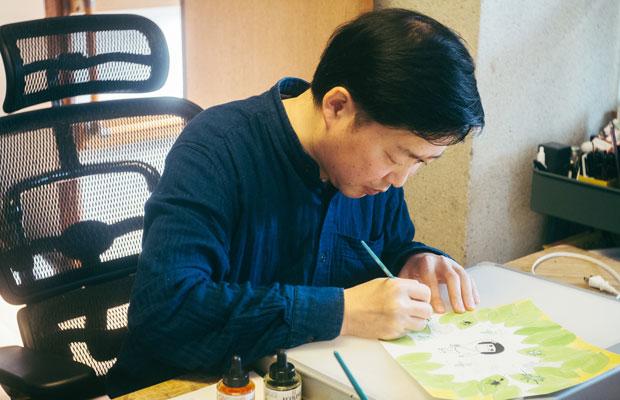 横山さんの作業スペースは家族の食卓。昼間は連絡などで仕事が中断してしまうため、家族が寝静まった深夜に集中して描くことが多いという。