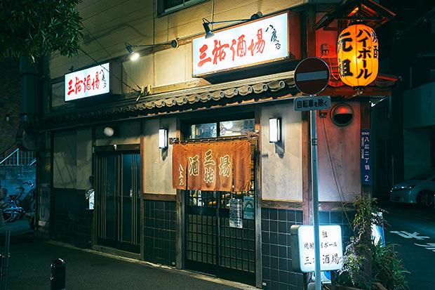 焼酎ハイボールを生み出した本店は、区画整理のため惜しまれつつ閉店しましたが、昭和41(1966)年、この家の三男だったマスターの父が開業した正統なのれん分け店である八広店が継承しています。最寄り駅は京成線と東武亀戸線の曳舟駅。徒歩7分ほど、明治通り沿いとその裏側の2か所にのれんがかかる。開放的でもあり、居心地良い秘密基地的な趣もあり。