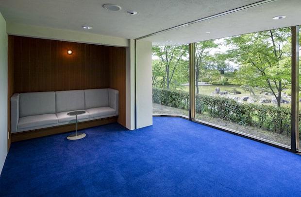 日本庭園が見える、静謐なムードのソファのある部屋。