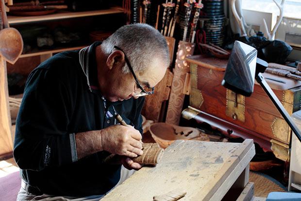 地元・二風谷をはじめ日本各地で、チセ造りの第一人者として熱心に取り組む、尾崎剛さん。イタやニマなどのほか、自然の木を使った置物など多彩な作品を制作しており、木彫り職人としても活躍中。