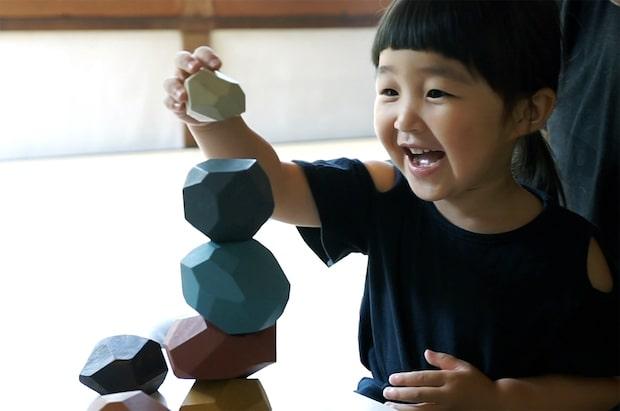 異なるサイズ・形状の〈tumi-isi(ツミイシ)〉を積み上げることで、子どもの想像力やバランス感覚が養われる。