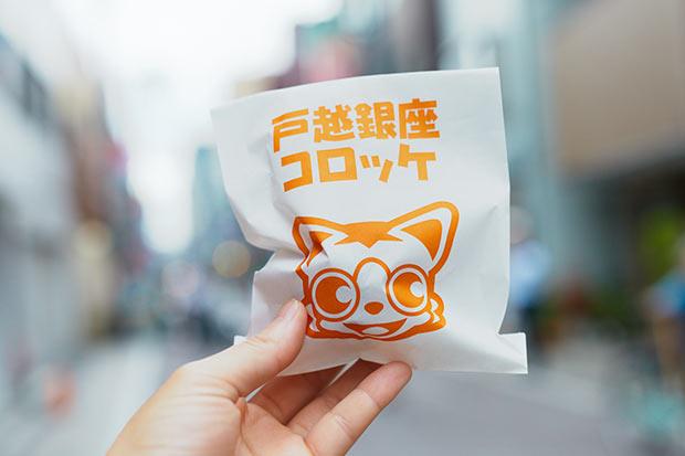 フライものを入れる袋に描かれているのは戸越銀座のマスコット、銀ちゃんこと戸越銀次郎。名前は硬派でもかわいらしい。「おでんコロッケ」1個108円。