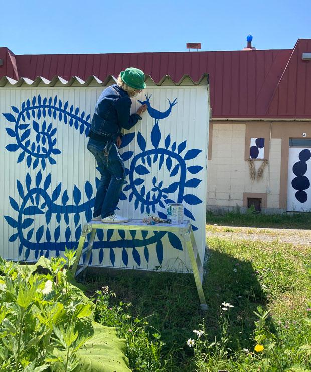 MAYAさんは、昨年アトリエのドアや窓に紺色の絵具で石を描き、今年は倉庫に植物の文様を描いた。美流渡がどんどん明るいムードになっているように思う。
