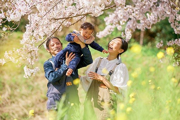 桜満開の中で笑顔をみせる、畠山千春さん、ご主人のコーイチさん、娘さんのショット