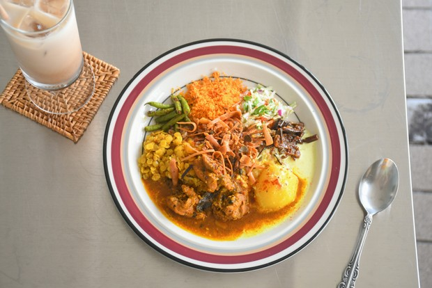 紅茶で炊いたライスの上に日替わりカレーや炒め物など8種類もの副菜が盛りつけられた「カーラヤカリヤ」。季節によって使う食材は変わる。チャイやコーラもスパイスをふんだんに用いた自家製。1200円(税込)