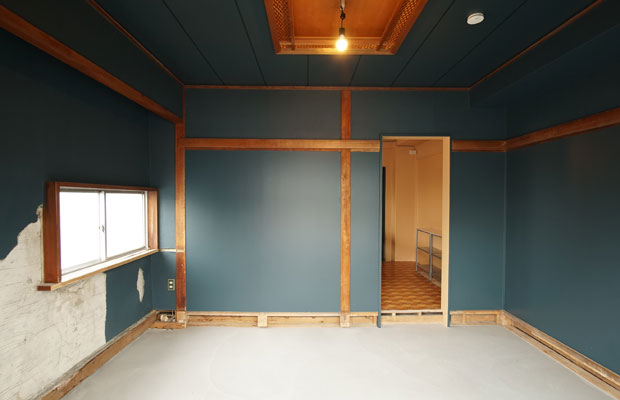 Room Aは床を土間にし、壁を深い青に塗装。新たに開口を設け、壁の剥がれた箇所はそのままに。