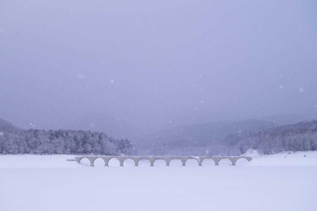しんしんと降り続く雪の中に佇む橋(2021年1月撮影)。