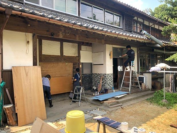 窓や玄関にベニヤ板を打ちつける作業風景写真