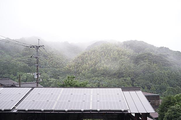 雲に覆われた空と、屋根に設置されたソーラーパネルの写真