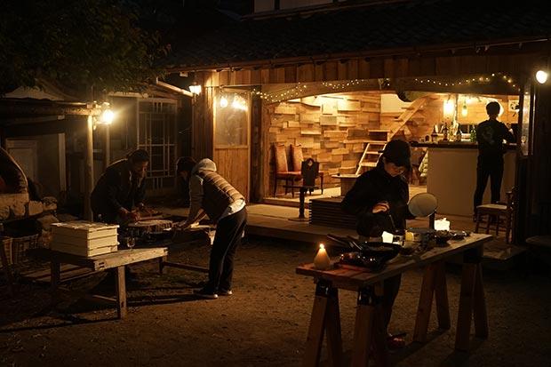 夜間のお庭でのピザパーティーの様子。ソーラーランタンのオレンジ色の光が空間を演出している写真