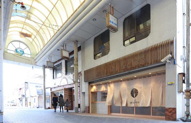 老舗の呉服店跡が湯浅豆腐店へ。もともとドアがなかったため、新たに開閉できる店舗ファサードを制作。できるだけ開放的にしながらも、中にいるお客さんが落ち着いて食事ができるようなファサードとした。