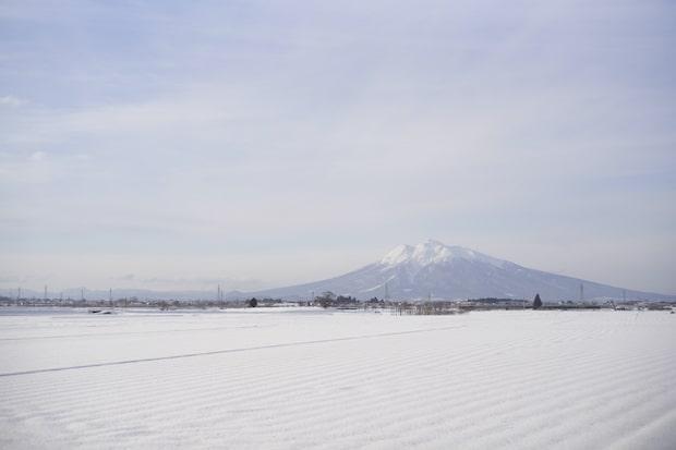 雪が降り積もる津軽平野と、その中心に位置する津軽のシンボル岩木山。冬の寒さが厳しい津軽内陸部ですが、夏は一転温暖で好天が続くため、雪解け水による稲作が盛んで、米を使った発酵食品が多く伝わります。(撮影:船橋陽馬)
